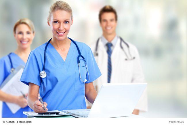 Krankenschwester mit Laptop, Arzt und Assistenz im Hintergrund