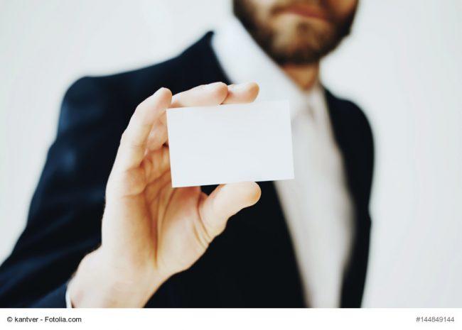 Mann im Anzug zeigt seine Visitenkarte