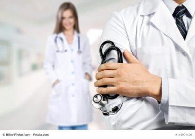 Arzt im Vordergrund, im Hintergrund lächelnde Ärztin