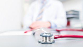 Arzt an seinem Schreibtisch, Stetoskop im Vordergrund