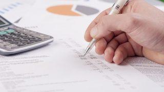 Hand mit Stift liegt auf Blättern mit Bilanzzahlen
