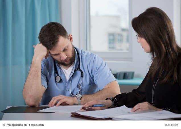 Arzt im Gespräch mit Finanzberaterin blickt auf Unterlagen
