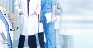 Ärztin mit Unterlagen und weitere Ärzte im Hintergrund