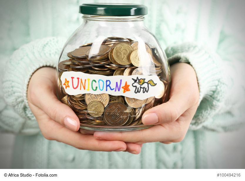 Frau hält Glas mit Geld und Aufschrift Unicorn in Händen