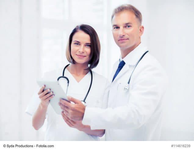 Arzt und Ärztin schauen auf Anzeige im Tablet