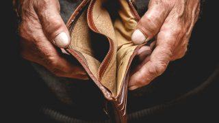 Ältere Person hält leeren Geldbeutel in die Kamera