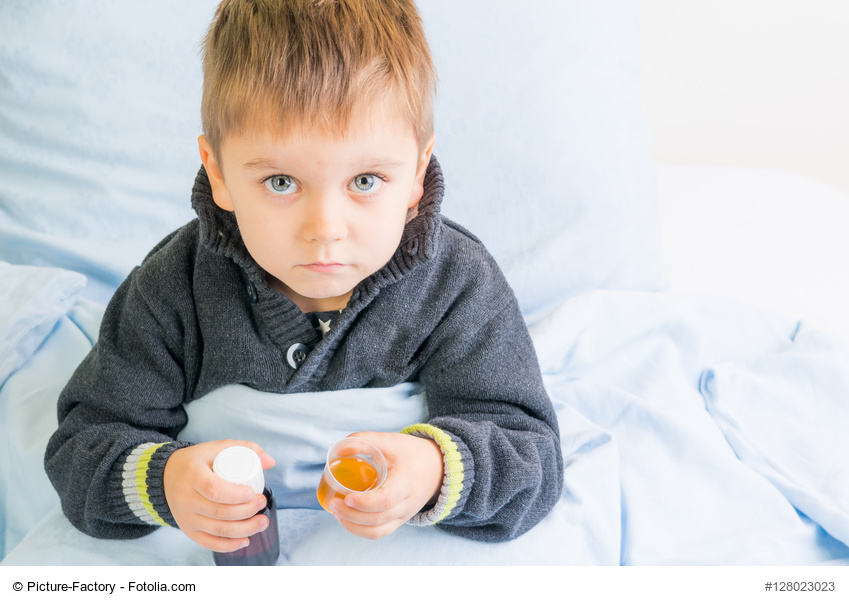 Kind liegt krank im Bett und hält Medikamente in den Händen
