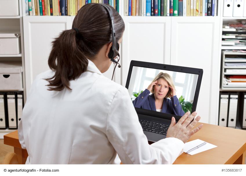 Ärztin berät Patienten über eine Video-Sprechstunde am Laptop