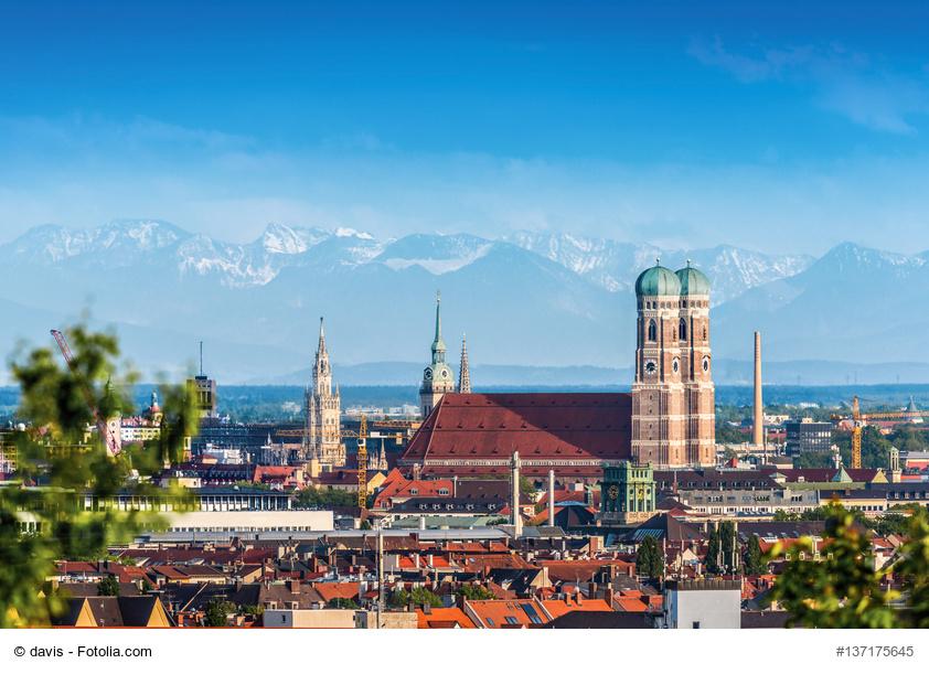 Blick auf Frauenkirche in München und Berge im Hintergrund