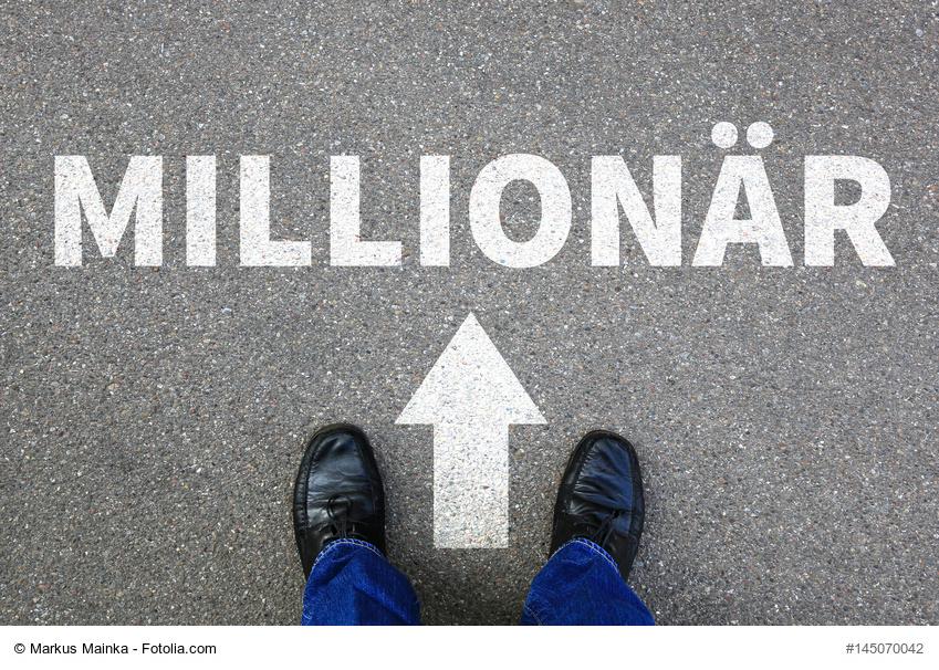 Millionär-Schriftzug auf dem Boden und Pfeil in Richtung vorne, davor steht ein Mann