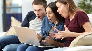 Zwei Frauen und ein Mann sitzen auf dem Sofa und schauen ins Laptop