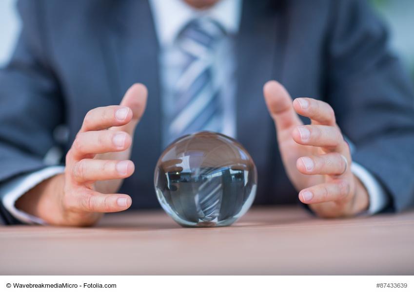 Mann im Anzug schaut in eine Glaskugel