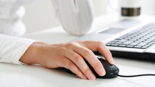 Frauenhand auf PC-Maus, Frau sitzt vor PC