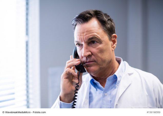 Arzt telefoniert in seiner Praxis