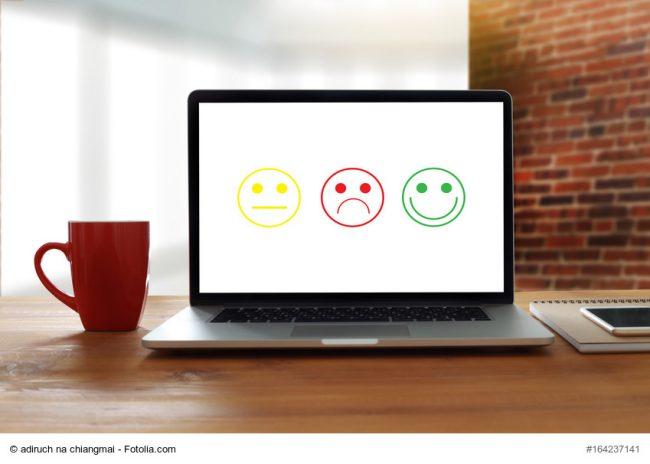 Laptop mit 3 Smileys auf dem Schirm, ein lachendes, ein neutrales und ein trauriges als Symbol für Bewertungsportale wie jameda