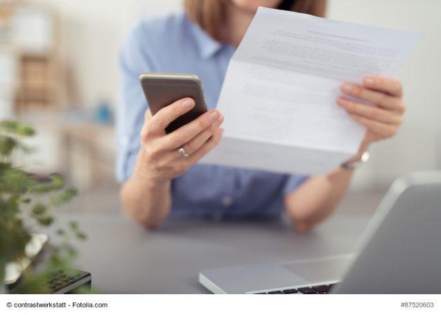 Frau blickt auf Rechnung und hält Smartphone in der Hand