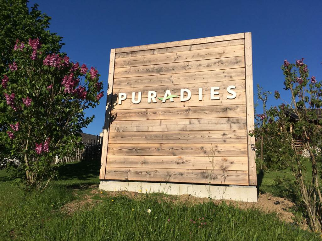 SChild am Eingang zum Chaletdorf Puradies mit Aufschrift Puradies