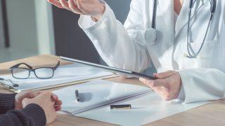 Ärztin sitzt am Schreibtisch und spricht mit Patienten
