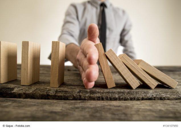 Hand zwischen umfallenden Holz-Dominosteinen