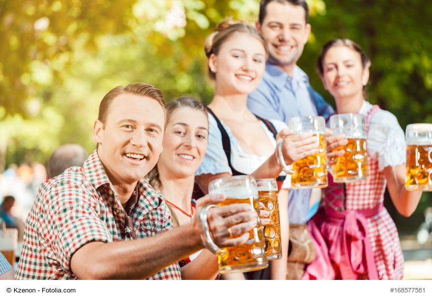 Gruppe junger Leute in Tracht und mit Bierkrügen im Biergarten