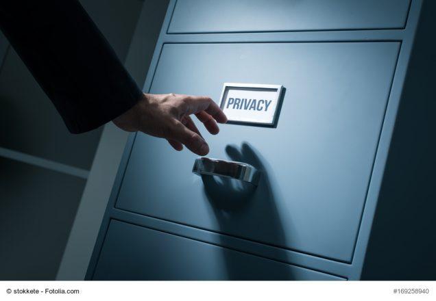 Hand greift nach Aktenschublade mit der Aufschrift Privacy