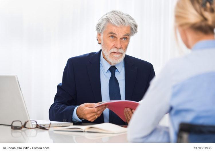 Mann im Anzug, Anwalt oder Arzt, sitzt am Schreibtisch und spricht mit Frau gegenüber