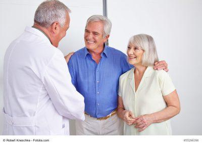 Arzt schüttelt Patienten die Hand, Patient und seine Frau strahlen