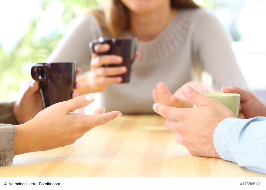 Frühstück: 2 Frauen und ein Mann reden und trinken Kaffee am Tisch