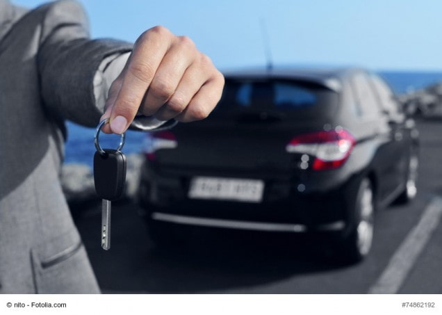 Mann hält einen Autoschlüssel in der Hand. Im Hintergrund steht ein Auto.