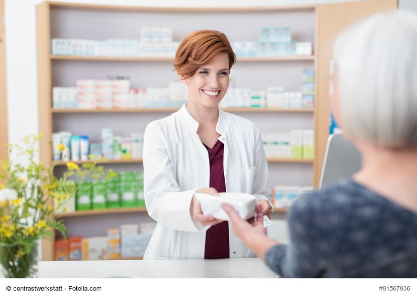 Apothekerin übergibt Arzneimittel an Patientin