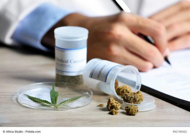 Cannabis in einer Dose und die Hand eines Arztes, die ein Rezept unterschreibt