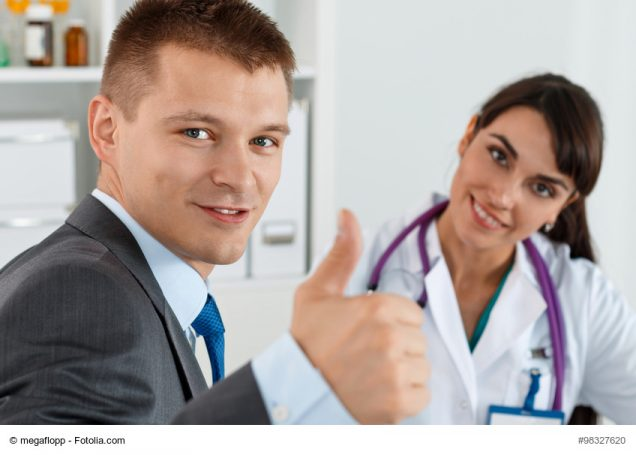 Mann beim Arzt hebt Daumen
