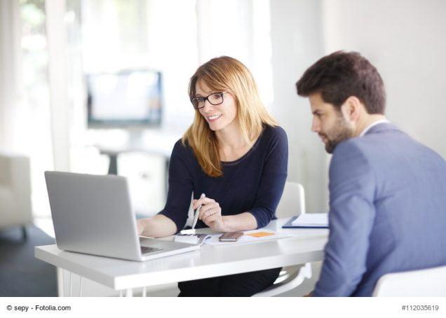 Business-Mann und Business-Frau sitzen am Schreibtisch und schauen auf ein Laptop