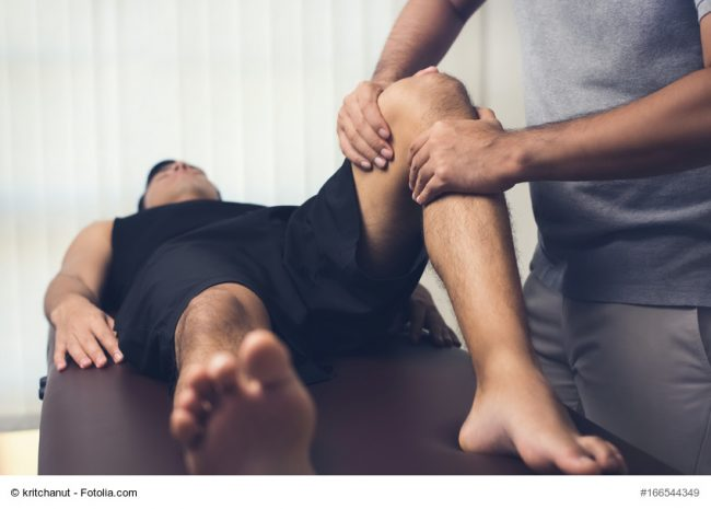 Male therapist massaging knee of athlete patient - sport physical therapy concept