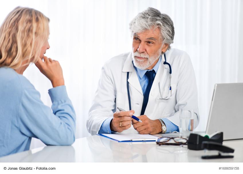 Älterer Arzt im Gespräch mit Patientin