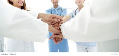 Ärzte, die die Hände übereinanderlegen