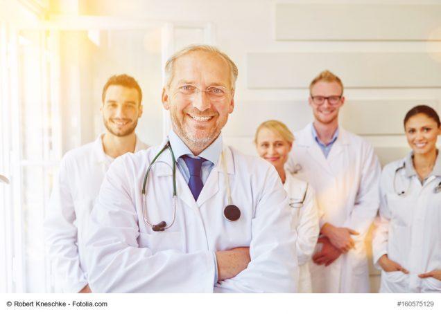 Zufriedener Chefarzt mit Ärzte Team im Rücken im Krankenhaus
