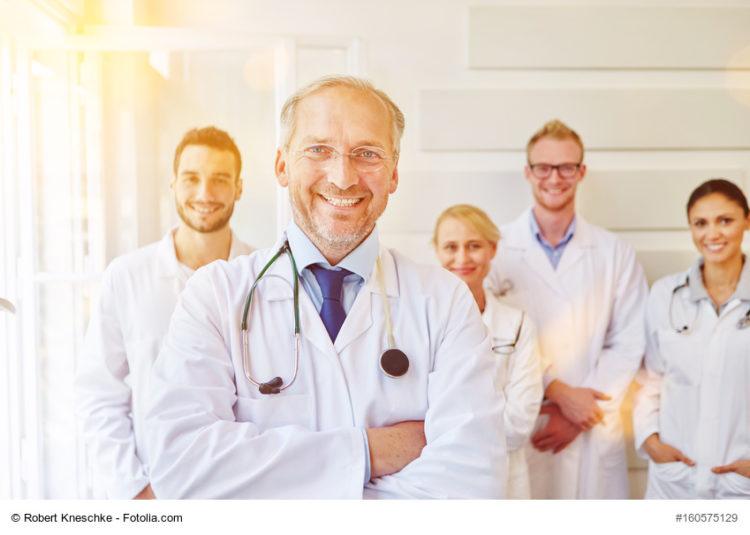 Zufriedener Chefarzt mit Ärzteteam im Rücken im Krankenhaus
