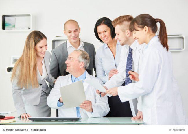 Klinik-Ärzte und -Mitarbeiter und ihr Chef freuen sich über ein Dokument