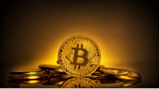 Bitcoin standing on the background of scattering of coins. The concept of developing a new virtual currency. Toning.
