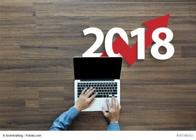 Mann am Laptop, im Hintergrund die Jahreszahl 2018 mit einem Kurs-Pfeil