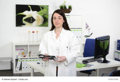 Junge Ärztin steht mit Stethoskop in der Hand in Arztpraxis