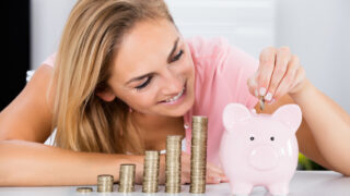 Happy Woman Inserting Coin In The Piggybank