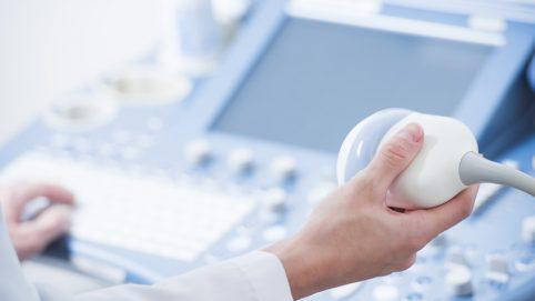 Hand, die ein Ultraschallgerät bedient