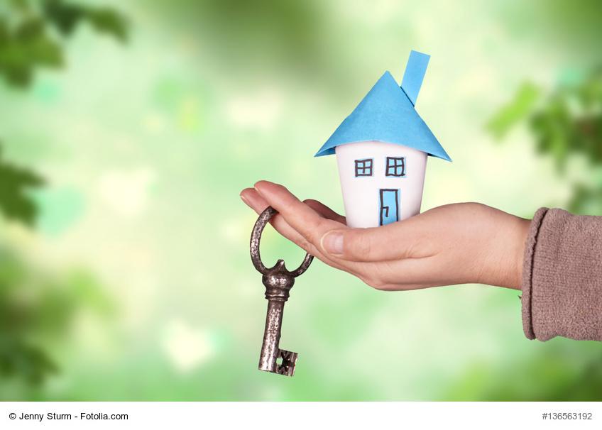 Hand mit Papierhaus und Schlüssel