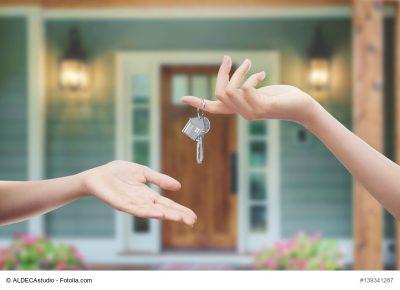 Immobilie übergeben Mani con chiavi con sfondo porta di casa