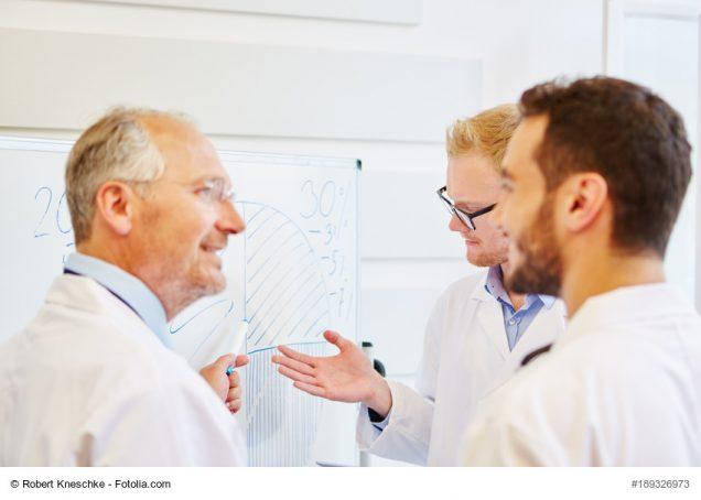 Ärzte diskutieren in einem Workshop zur Fortbildung am Flipchart