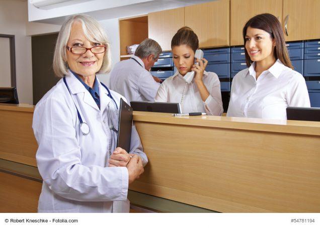 Ärztin und Rezeptionistin am Empfang in einem Krankenhaus