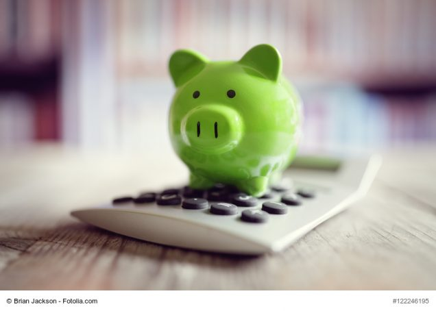 Piggy bank on calculator concept for saving, accounting, Zinssicherung, banking and business account