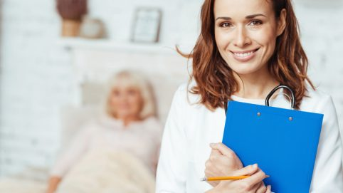 Ready to help. Cheerful delighted professioanal doctor holding folder and smiling while visiting her patient at home